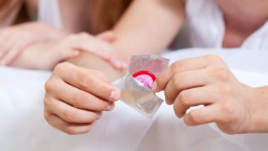 condom-wrapper-being-opened-by-couple-in-bed-trying-to-avoid-getting-pregnant